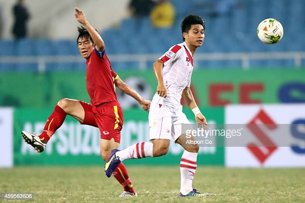 Le Tan Tai of Vietnam battles Phoutdavy Phommasane of Laos during the 2014 AFF Suzuki Cup Group A match between Laos and Vietnam at the My Dinh...