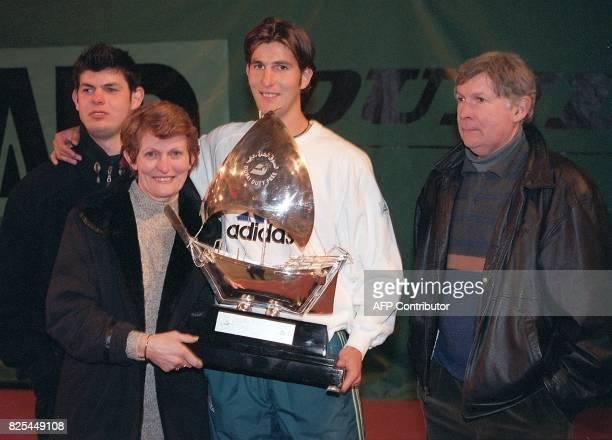 le tennisman français Jerôme Golmard pose le 15 février à Dijon avec ses parents Liliane et Roger et son frère Yannick avec le trophée qu'il a...