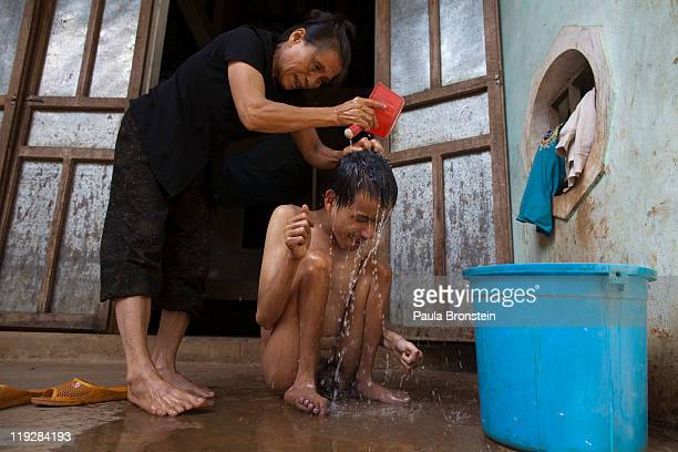 Le Thi Mit bathes her son Nguyen VanTrong at their home on March 7 in Cam Lo Quang Tri district Vietnam his handicap was caused due to the effects of...
