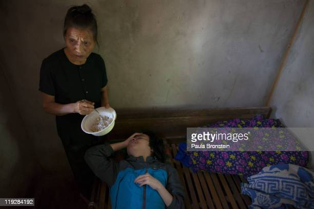 Le Thi Mit feeds her son Nguyen Van Choui at their home on March 7 in Cam Lo Quang Tri district Vietnam his handicap was caused due to the effects of...