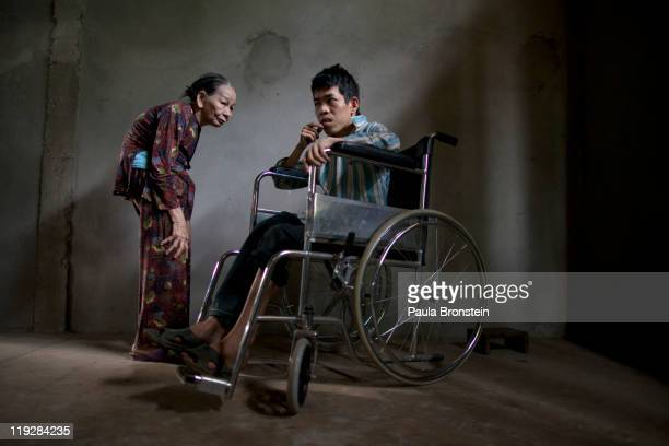 Le Van Khanh38 stands next to his mother Nguyen Thi Huyen March 8 in Cam Lo in Quang Tri province Vietnam Le Van was born deaf mentally handicapped...