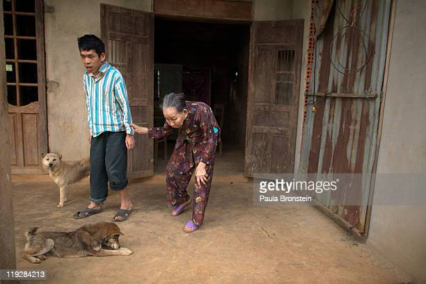 Le Van Khanh38 walks with his mother Nguyen Thi Huyen March 8 in Cam Lo in Quang Tri province Vietnam Le Van was born deaf mentally handicapped with...
