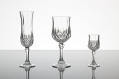 """A champagne flute, wine glass and liqueur glass made out of cut glass (crystal glass or lead glass), on plain gray shiny surface with gray background"""