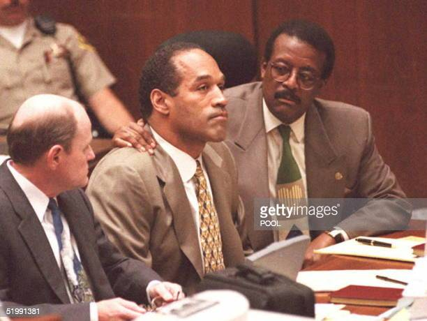 Lead defense attorney Johnnie Cochran puts his arm on OJ Simpson's shoulder after Simpson told Judge Lance Ito 22 September that he has faith that...