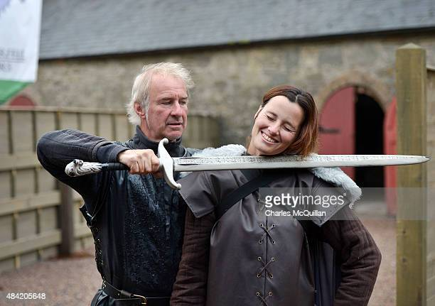 Lead Game of Thrones tour instructor William Kells prepares to 'behead' a tourist as part of the Winterfell experience at Castle Ward on August 13...