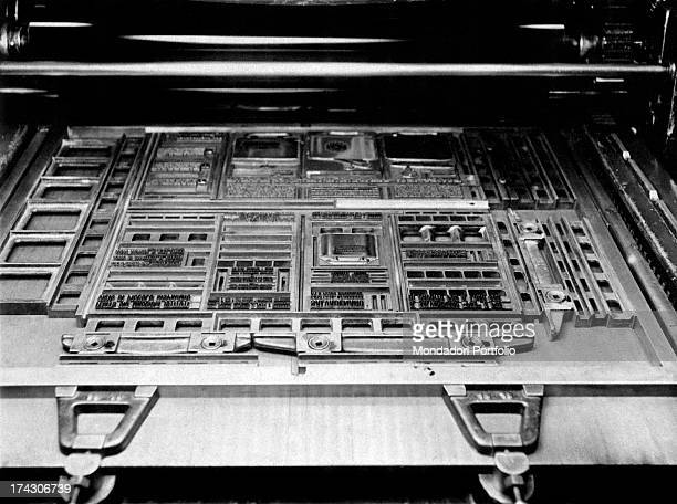 Lead pages put in the right order in the printing press Above them the ink rollers that will impress the ink on the pages 1950s