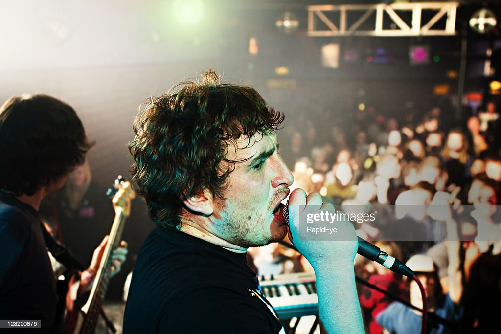 Lead singer gives his all to fans at a concert : Stock Photo