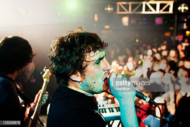 Cantor principal proporciona a todos os fãs em um concerto de música