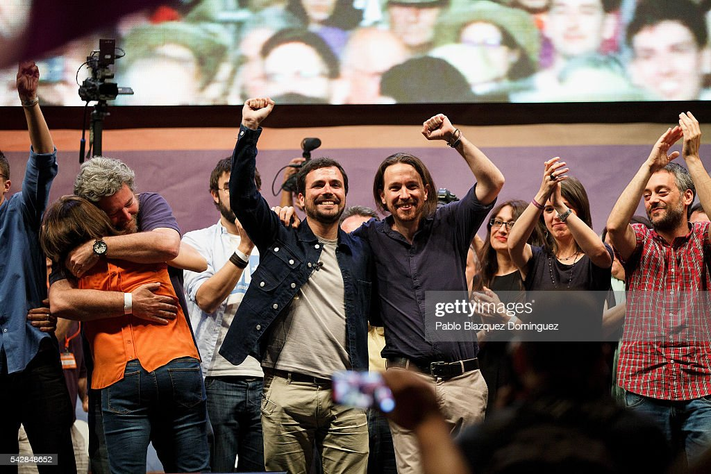 Leader and candidate of left wing alliance party Unidos Podemos 'United We Can' Pablo Iglesias (R) and party member Alberto Garzon (L) rise their fist towards their supporters during a rally ahead of Spanish General Elections on June 24, 2016 in Madrid, Spain. Spanish voters head back to the polls on June 26 after the last election in December failed to produce a government. Latest opinion polls suggest the Unidos Podemos 'United We Can' left-wing alliance could make enough gains to come in second behind the caretaker government of the center-right Popular Party.