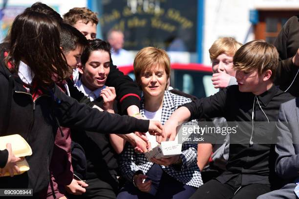 SNP leader and First Minister Nicola Sturgeon shares her fish and chips with some passing schoolchildren on the general election campaign trail in...
