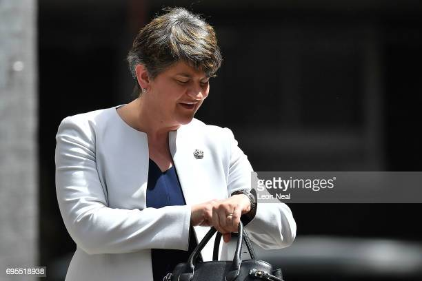 DUP leader Arlene Foster checks her watch as she arrives at 10 Downing Street on June 13 2017 in London England Discussions between the DUP and the...