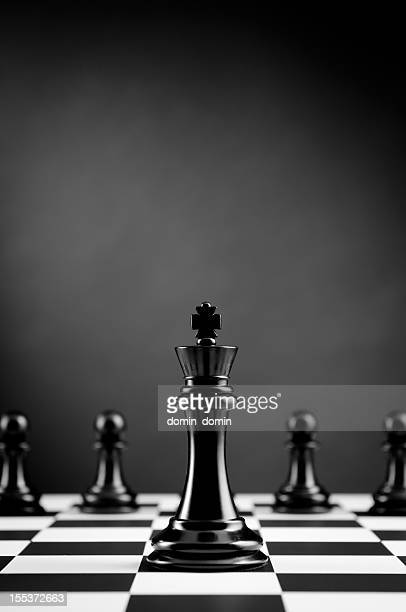 Leader, Black Chess King against chess pawns on dark background