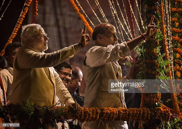 BJP leader Narendra Modi and Rajnath Singh gesture to the crowd after they performed the Hindu Ganga Puja prayer ritual at the Dashaswamadeh Ghat on...