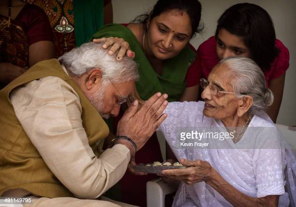 BJP leader Narendra Modi is blessed by his mother Heeraben Modi on her front porch after seeking her blessing on May 16 2014 in Ahmedabad India Early...