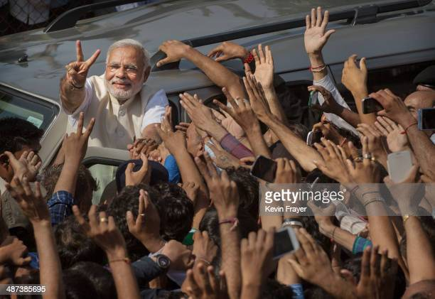 BJP leader Narendra Modi shows his inked finger to supporters as he leaves a polling station after voting on April 30 2014 in Ahmedabad India India...