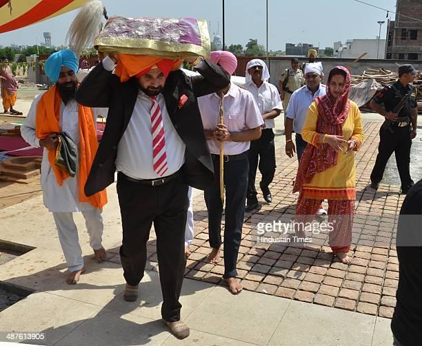 BJP leader Navjot Singh Sidhu along with his wife Dr Navjot Kaur Sidhu member of Punjab Legislative Assembly carrying the Guru Granth Sahib to...