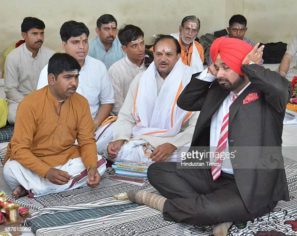 BJP leader Navjot Singh Sidhu offers prayer after establishes the Guru Granth Sahib and Shivling in his new house on May 1 2014 in Amritsar India...