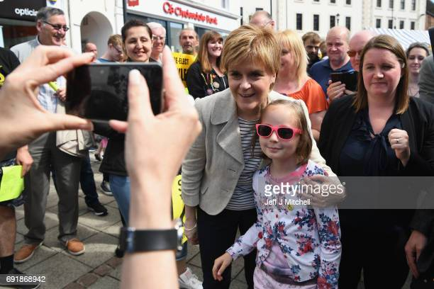 SNP leader Nicola Sturgeon poses for a photo with a young supporter while campaigning for the General Election on June 3 2017 in Dumfries Scotland As...