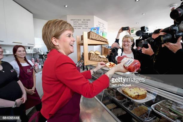 SNP leader Nicola Sturgeon serves a bacon roll in a cafe as she campaigns with the candidate for East Lothian George Kerevan on May 17 2017 in...