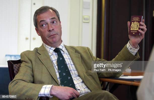 Leader Nigel Farage holds up his passport as he is being interviewed by the Press Association in Belfast during a one day visit to the province where...