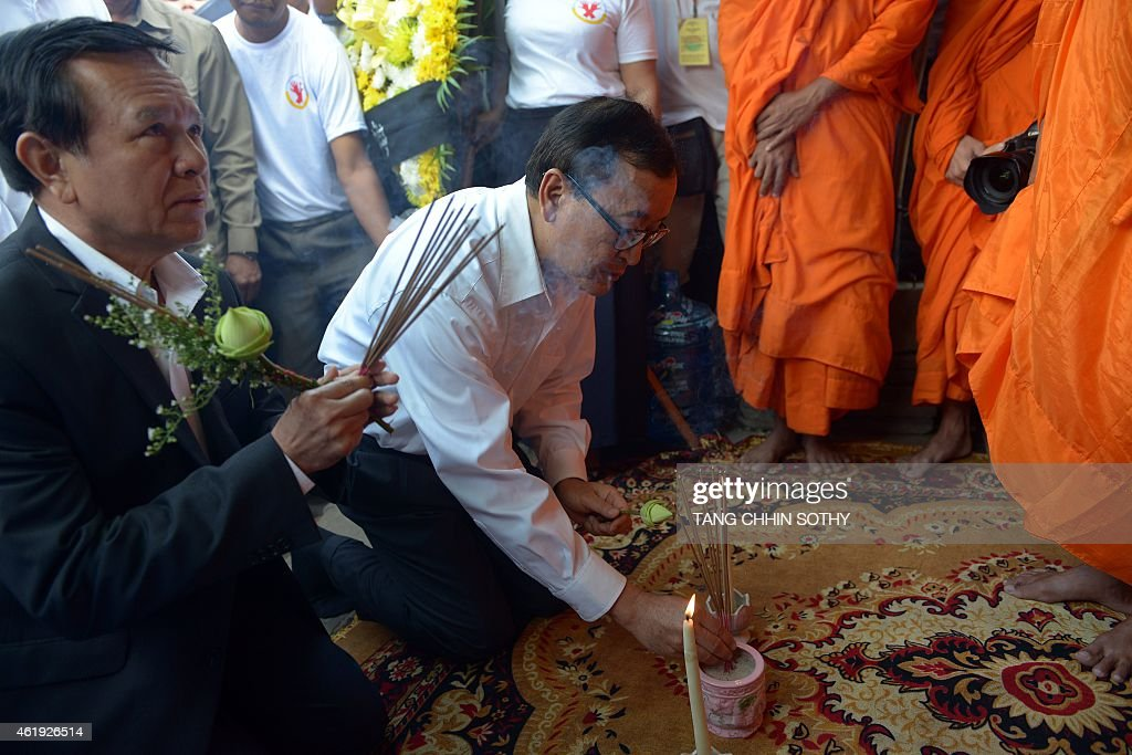 Leader of Cambodia National Rescue Party (CNRP) <a gi-track='captionPersonalityLinkClicked' href=/galleries/search?phrase=Sam+Rainsy&family=editorial&specificpeople=660347 ng-click='$event.stopPropagation()'>Sam Rainsy</a> (C) and deputy of CNRP <a gi-track='captionPersonalityLinkClicked' href=/galleries/search?phrase=Kem+Sokha&family=editorial&specificpeople=659005 ng-click='$event.stopPropagation()'>Kem Sokha</a> (L) pray as they mark the 11th anniversary of the death of labour leader Chea Vichea, in Phnom Penh on January 22, 2015. Cambodian trade union members and workers on January 22, marked the 11th anniversary of the death of the prominent labour leader, calling for an end to the brutal killing of uninionists.