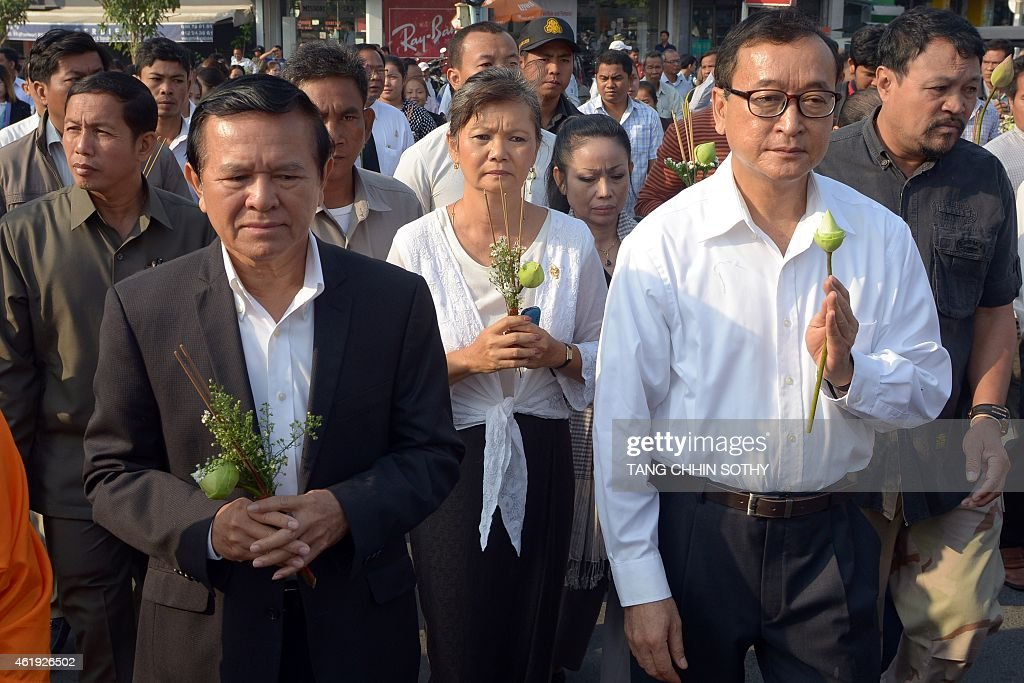 Leader of Cambodia National Rescue Party (CNRP) <a gi-track='captionPersonalityLinkClicked' href=/galleries/search?phrase=Sam+Rainsy&family=editorial&specificpeople=660347 ng-click='$event.stopPropagation()'>Sam Rainsy</a> (R), deputy of CNRP <a gi-track='captionPersonalityLinkClicked' href=/galleries/search?phrase=Kem+Sokha&family=editorial&specificpeople=659005 ng-click='$event.stopPropagation()'>Kem Sokha</a> (C) and workers march to mark the 11th anniversary of the death of labour leader Chea Vichea, in Phnom Penh on January 22, 2015. Cambodian trade union members and workers on January 22, marked the 11th anniversary of the death of the prominent labour leader, calling for an end to the brutal killing of uninionists.