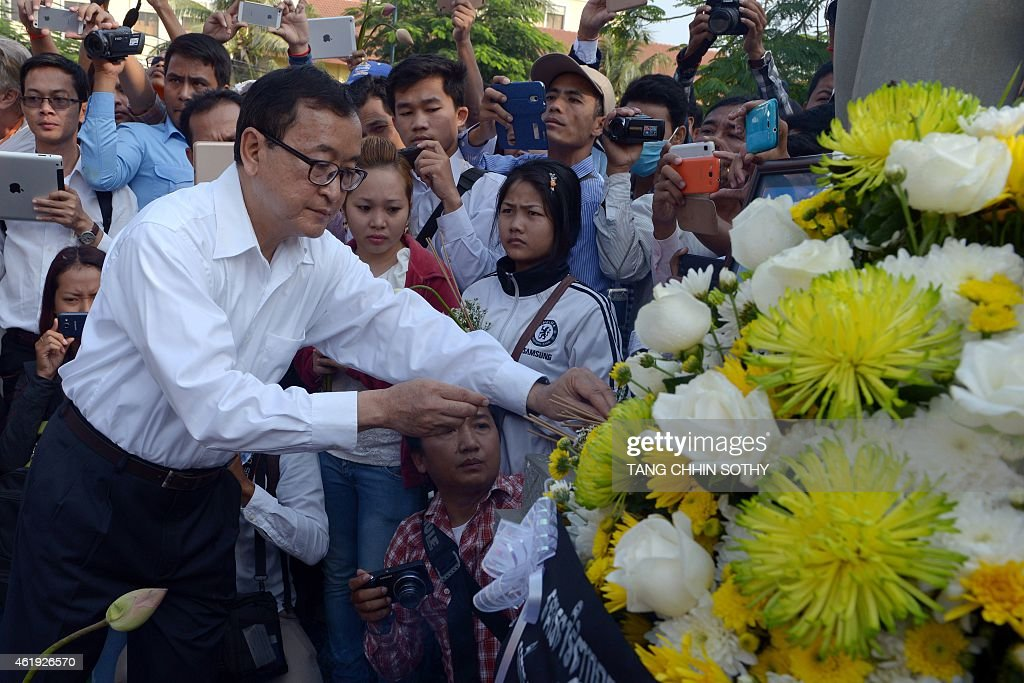 Leader of Cambodia National Rescue Party Sam Rainsy lays flowers as he prays to mark the 11th anniversary of the death of labour leader Chea Vichea...