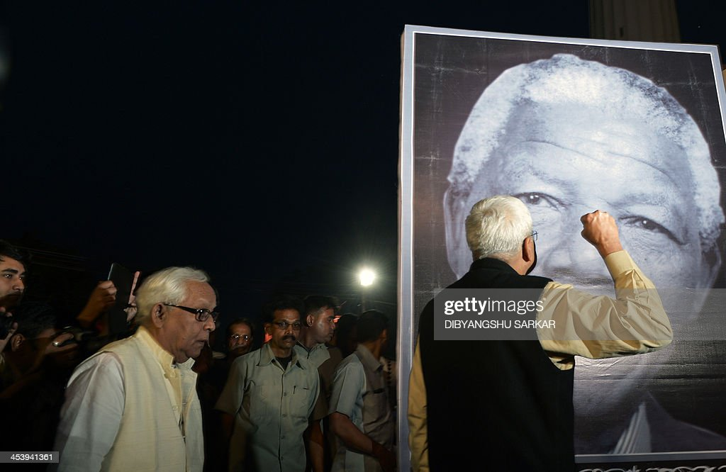 Leader of Communists Party of India (Marxist) Budhadeb Bhattacharya (L) and Prakash Karat (R) pay homage in front of a portrait of South African former president Nelson Mandela on the sidelines of a rally in Kolkata on December 6, 2013. Mandela, the revered icon of the anti-apartheid struggle in South Africa and one of the towering political figures of the 20th century, has died aged 95. Mandela, who was elected South Africa's first black president after spending nearly three decades in prison, had been receiving treatment for a lung infection at his Johannesburg home since September, after three months in hospital in a critical state. AFP PHOTO/Dibyangshu SARKAR