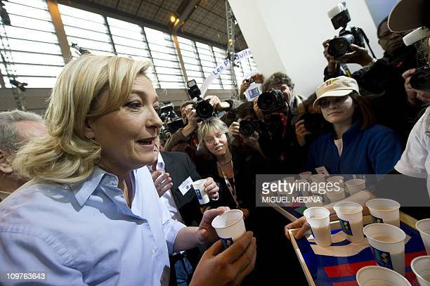 Leader of France's farright National Front party Marine Le Pen tastes a glass of milk on February 25 as she visits the Paris international...
