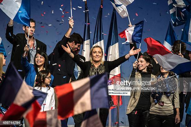 Leader of France's farright National Front party Marine Le Pen waves at the audience on November 30 2014 in Lyon as she arrives to deliver the...
