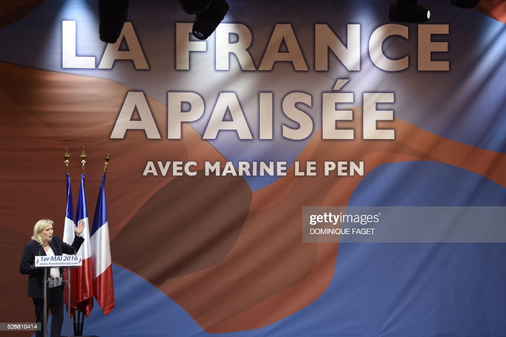 Leader of French far-right party Front National (FN) Marine Le Pen gives a speech during a party meeting on May 1, 2016 in Paris. On the background, the slogan 'An appeased France with Marine Le Pen' is seen. / AFP / DOMINIQUE
