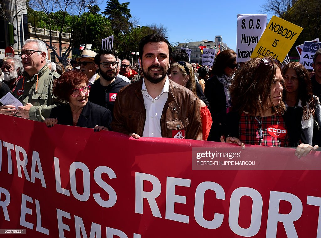 Leader of Izquierda Unida (United Left) Alberto Garzon stands behind a banner during the traditional May Day rally in Madrid on May 1, 2016. / AFP / PIERRE
