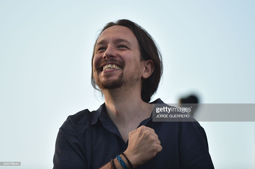 Leader of left wing party Podemos and party candidate, Pablo Iglesias puts his fist on his heart during the partys final campaign meeting in Madrid on June 24, 2016 ahead of the June 26 general election. / AFP / JORGE