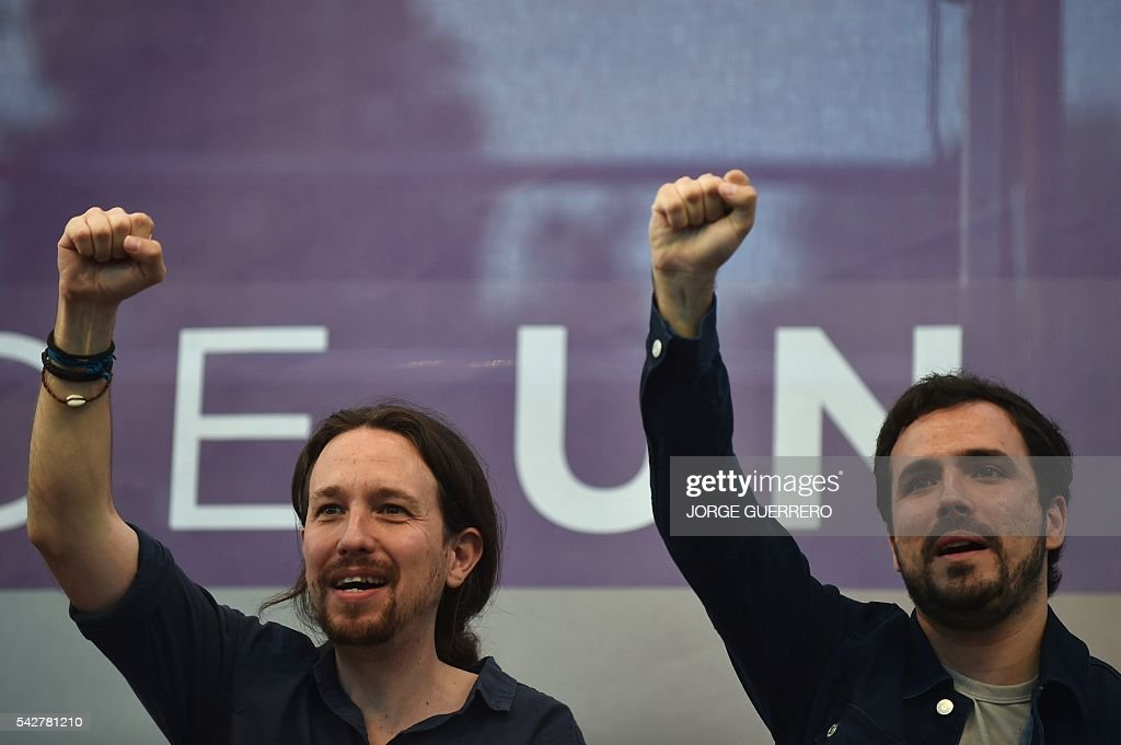 Leader of left wing party Podemos and party candidate, Pablo Iglesias (L) and leader of left-wing party IU Alberto Garzon raise their fist during the partys final campaign meeting in Madrid on June 24, 2016 ahead of the June 26 general election. / AFP / JORGE