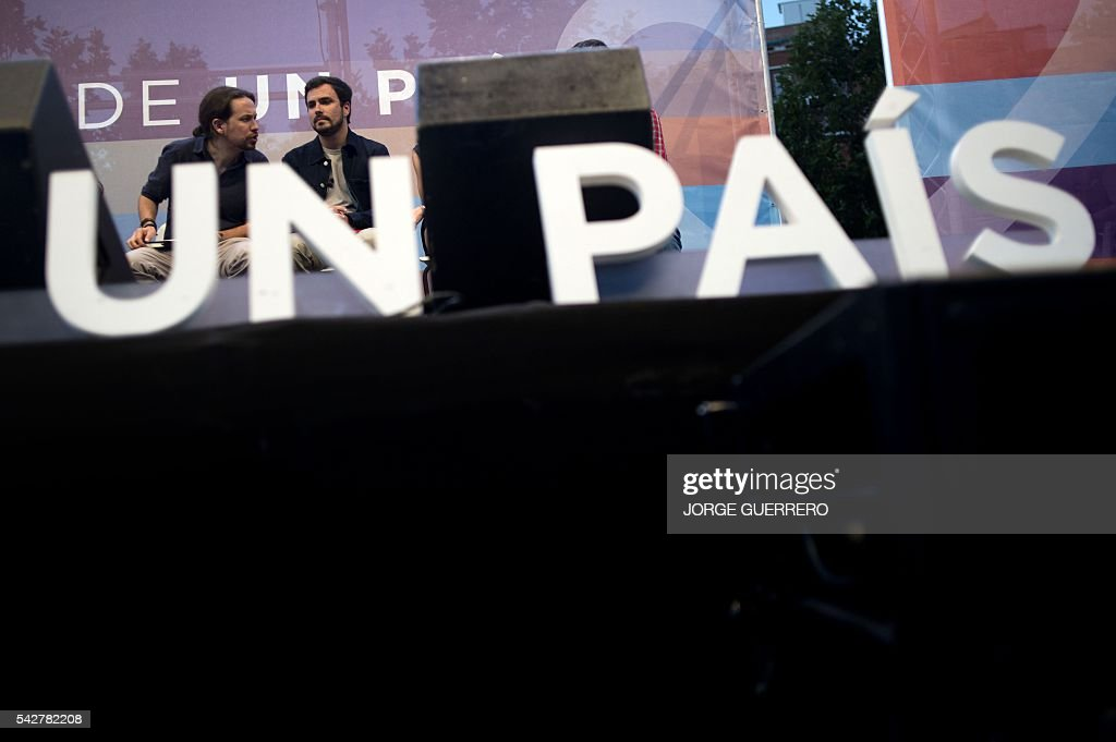 Leader of left wing party Podemos and party candidate Pablo Iglesias (L) chats with left-wing party IU featuring its leader Alberto Garzon during the partys final campaign meeting in Madrid on June 24, 2016 ahead of the June 26 general election. Spain votes again on June 26, six months after an inconclusive election which saw parties unable to agree on a coalition government. GUERRERO