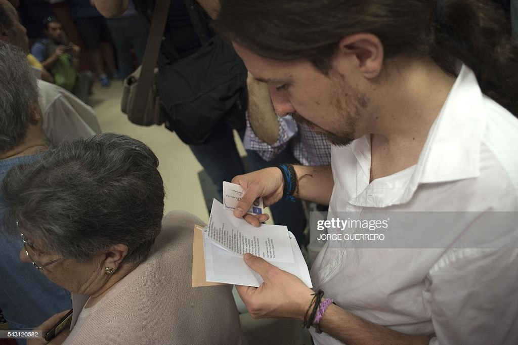 Leader of left wing party Podemos and party candidate, Pablo Iglesias, looks at his ballot for Spains general election at a polling station in cental Madrid on June 26, 2016. Spain votes today, six months after an inconclusive election which saw parties unable to agree on a coalition government. GUERRERO
