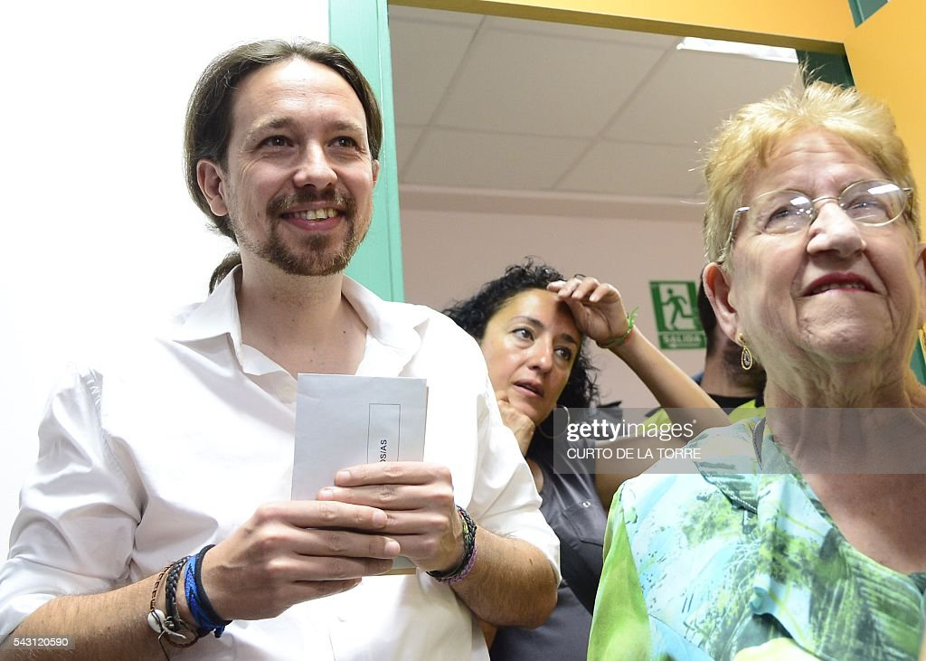 Leader of left wing party Podemos and party candidate, Pablo Iglesias, (L) waits to vote in Spains general election at a polling station in cental Madrid on June 26, 2016. Spain votes today, six months after an inconclusive election which saw parties unable to agree on a coalition government. TORRE