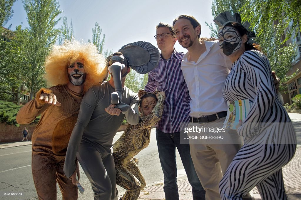 Leader of left wing party Podemos and party candidate, Pablo Iglesias, (2R) and Policy secretary of left-wing party Podemos Inigo Errejon pose with people dressed as cartoon animals as they arrive to vote in Spains general election at a polling station in cental Madrid on June 26, 2016. Spain votes today, six months after an inconclusive election which saw parties unable to agree on a coalition government. GUERRERO