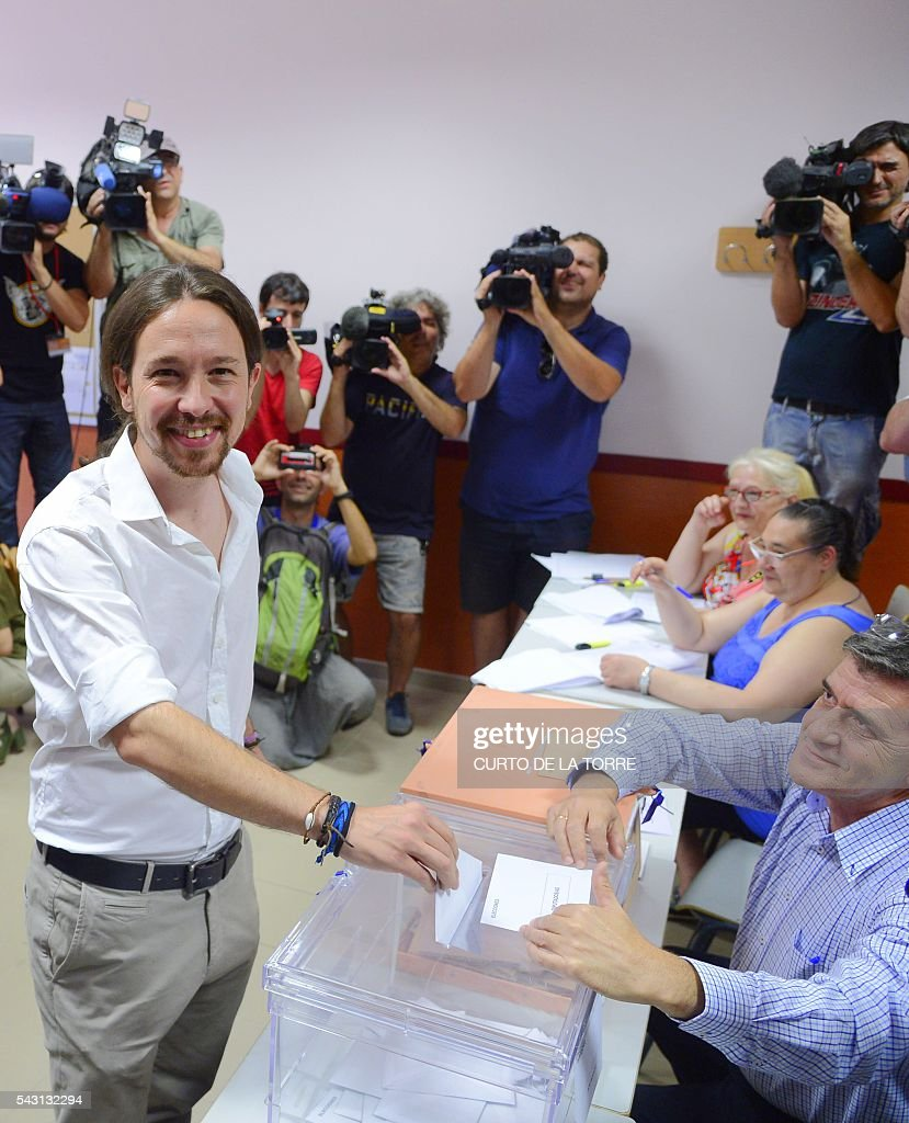 Leader of left wing party Podemos and party candidate, Pablo Iglesias, (C) vote in Spains general election at a polling station in cental Madrid on June 26, 2016. Spain votes today, six months after an inconclusive election which saw parties unable to agree on a coalition government. TORRE