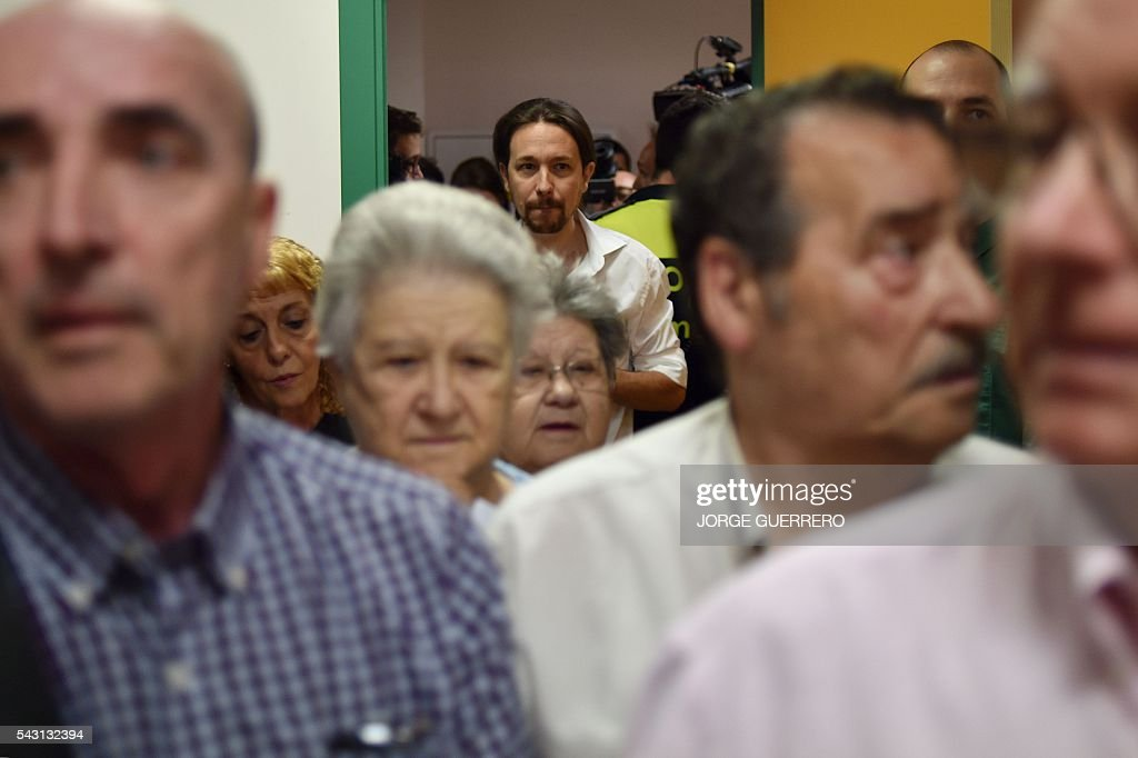 Leader of left wing party Podemos and party candidate, Pablo Iglesias, (C BACK) queues to vote in Spains general election at a polling station in cental Madrid on June 26, 2016. Spain votes today, six months after an inconclusive election which saw parties unable to agree on a coalition government. GUERRERO