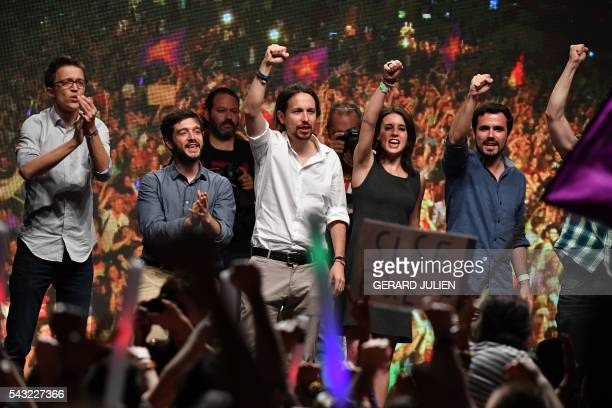 Leader of left wing party Podemos and party candidate Pablo Iglesias raises his fist with leftwing Podemos member and Madrid candidate congress the...