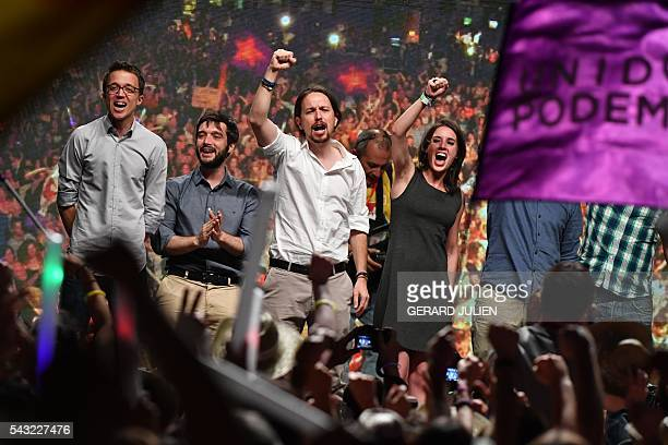 Leader of left wing party Podemos and party candidate Pablo Iglesias raises his fist with Leftwing Podemos member Irene Montero next to Policy...