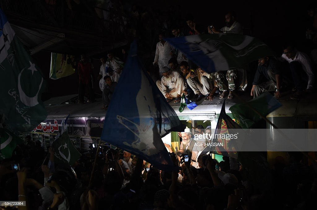 Leader of Pakistani Jamaat-i-Islami (JI) Siraj-ul-Haq (C) gets out from a train upon his arrival at a railway station in Karachi on May 27, 2016, at the end of train march. Haq said that the purpose of the Train March against corruption is to awake the people against corruption and the corrupt people. / AFP / ASIF