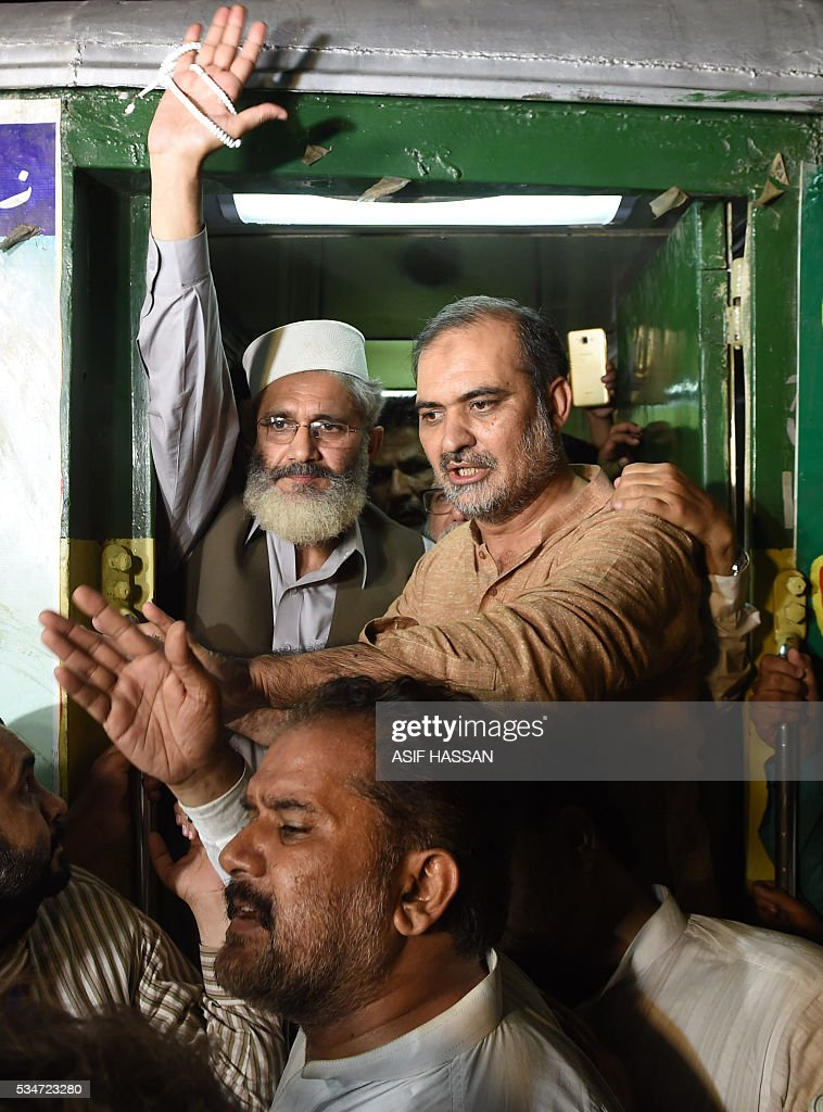 Leader of Pakistani Jamaat-i-Islami (JI) Siraj-ul-Haq (L) waves to supporters from a train upon his arrival at a railway station in Karachi on May 27, 2016, at the end of train march. Haq said that the purpose of the Train March against corruption is to awake the people against corruption and the corrupt people. / AFP / ASIF