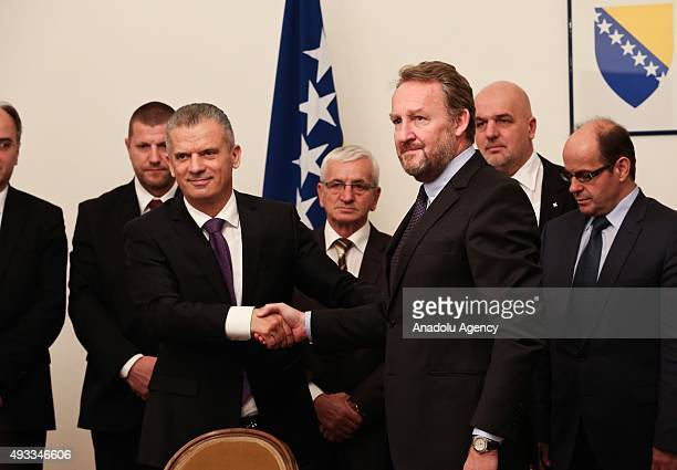 Leader of Party of Democratic Action Bakir Izetbegovic shakes hands with Leader of Union for a Better Future Fahrudin Radoncic after they signed a...