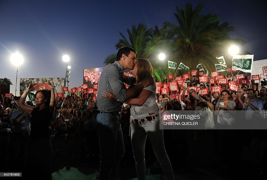 Leader of Spanish Socialist Party (PSOE) and party candidate Pedro Sanchez (L) kisses President of the regional Government of Andalucia Susana Diaz during the party's final campaign meeting in Sevilla on June 24, 2016 ahead of the June 26 general election. Spain is holding its second elections in six months, on June 26, after being governed by a caretaker government with limited powers since the December 20 polls put an end to the country's traditional two-party system as voters fed up with austerity and corruption scandals flocked to new groups. / AFP / CRISTINA