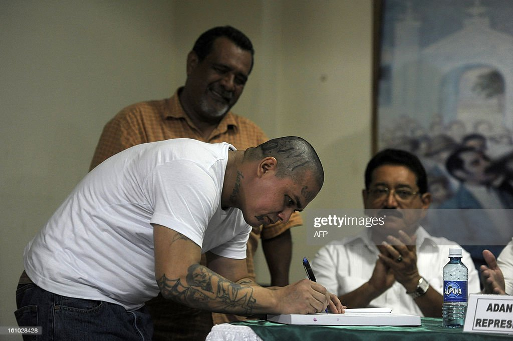 A leader of the MS-13 gang signs a statment about their decision to stop homicides, at the City Hall of the city of Sonsonate, 65 Km west of San Salvador, on February 8, 2012. Leaders of the MS-13 and 18th Street gangs agreed to stop homicides in the city of Sonsonate, as part of the truce process between gangs to reduce crimes in El Salvador. AFP PHOTO/Jose CABEZAS
