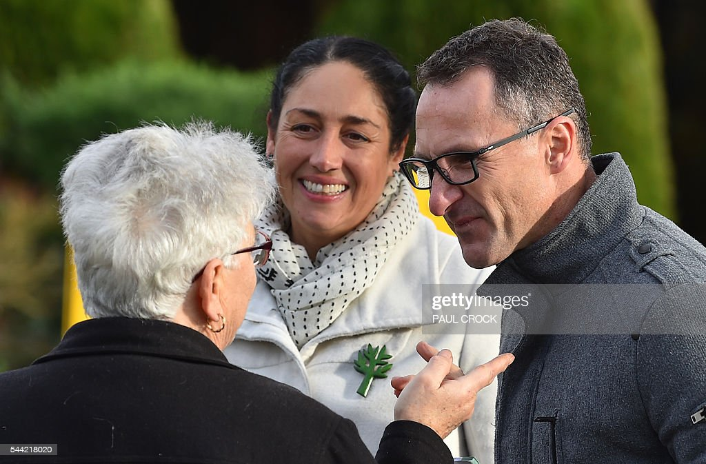 Leader of the Australian Greens Party Richard Di Natale (R) and Greens candidate for the seat of Batman Alex Bhathal (C) talk to a voter ahead of casting their votes in the Australian Federal Election in Melbourne on July 2, 2016. Australia is voting in a general election which is expected to be a close race between the ruling Liberal-National coalition and the opposition Labor Party. / AFP / Paul Crock