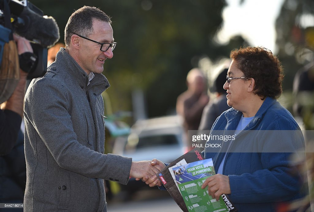 Leader of the Australian Greens Party Richard Di Natale (L) shakes hands with an elderly voter at a polling booth in the northern seat of Batman in the Australian Federal Election in Melbourne on July 2, 2016. Australia is voting in a general election which is expected to be a close race between the ruling Liberal-National coalition and the opposition Labor Party. / AFP / Paul Crock