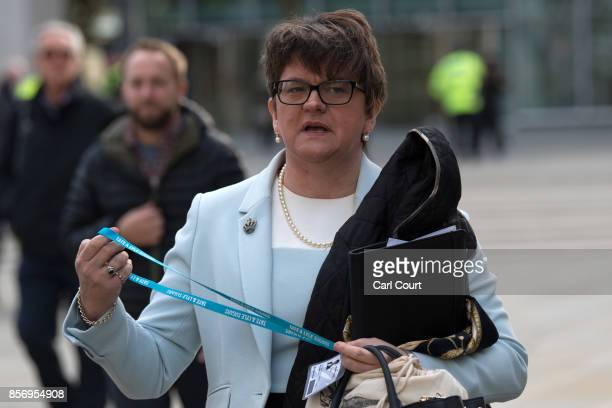 Leader of the Democratic Unionist Party Arlene Foster puts on her conference identity as she walks from Manchester Town Hall after a question and...